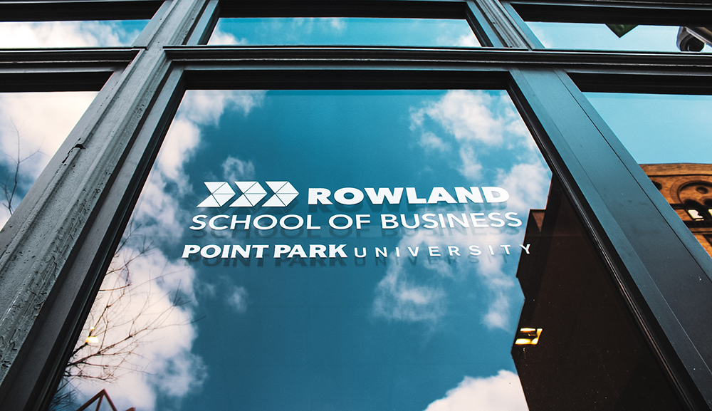 Pictured is the Rowland School of Business logo on a window with clouds reflecting on the glass. Photo by Nathaniel Holzer.