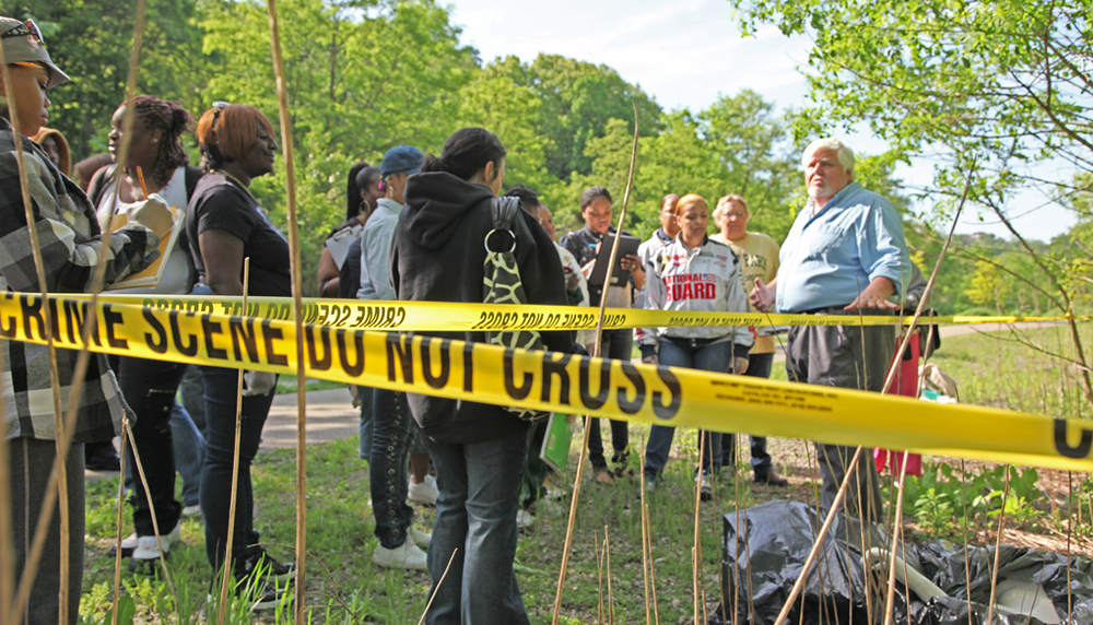 Pictured is Assistant Professor Edward Strimlan, M.D., conducting a mock crime scene investigation with forensic science students in Schenley Park. | Photo by Andy Weier