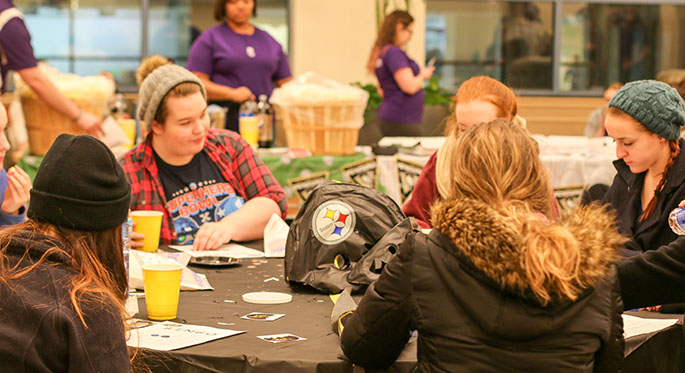 Point Park students sit at a round table decorated in black and gold while playing 412 Bingo, named for Pittsburgh's area code, at the University's first-ever Yinzer Park Feb. 18 in Lawrence Hall. | Photo by Victoria A. Mikula