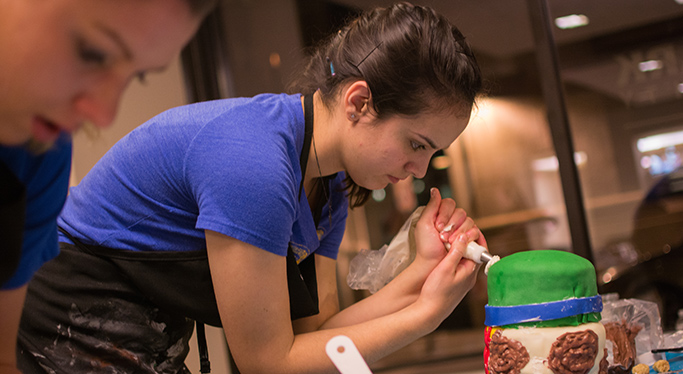 A student decorates a cake with an icing bag during the cake-off, Point Park's annual cake decorating competition.