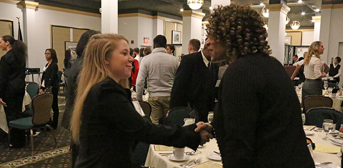 Two women smile and shake hands at Point Park University's annual Networking Reception and Etiquette Dinner 2015. | Photo by Victoria A. Mikula