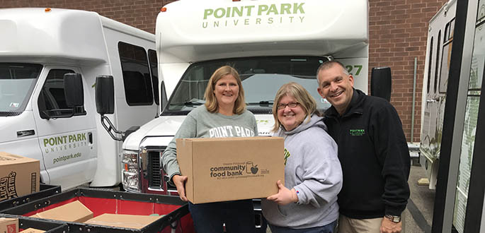 Heather Starr Fiedler, director of the Department of Community Engagement, Veronika Panagiotou, doctoral student, and Keith Paylo, vice president of student affairs and dean of students, prepare to stock Pioneer Pantry on campus.