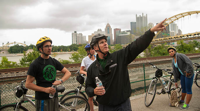 With the Pittsburgh skyline in the background, Point Park President Paul Hennigan points out a feature of the city landscape during a stop on his annual bike ride with a group of Point Park students. | Photo by Christopher Rolinson