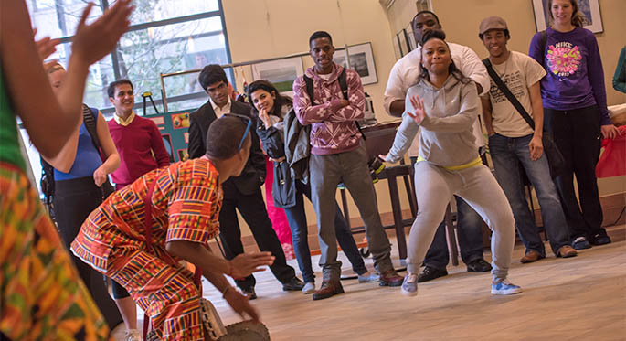 A female Point Park student steps out to try African dance accompanied by a drummer from the Legacy Arts Project African dance troupe at the 6th Annual Cultural Summit Oct. 15 in Lawrence Hall. | Photo by Christopher Squier
