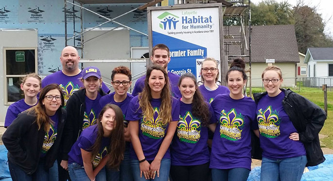 A group of Point Park students pose for a group shot at the Habitat for Humanity work site outside New Orleans, La., where they volunteered their time during spring break, 2015.
