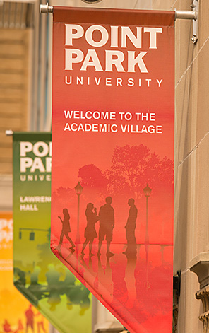 A red banner displaying the Point Park logo welcomes visitors to the Academic Village.