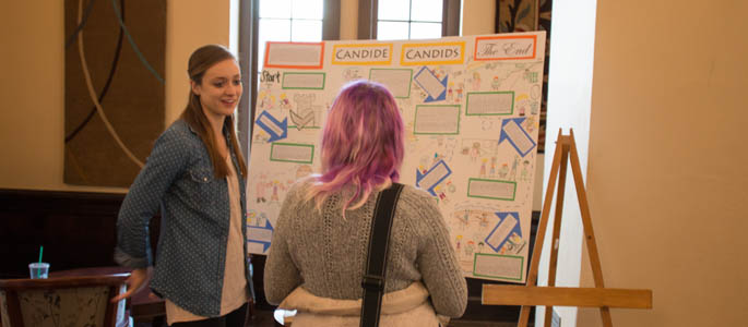 A student discusses her research poster with another student at the 2015 Humanities and Human Sciences Symposium. | Photo by Victoria A. Mikula