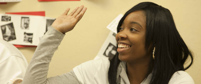 Pictured is a Point Park University student raising her hand in the classroom.