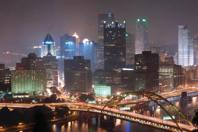Pictured is the skyline of Downtown Pittsburgh at night with a view of the Wyndham Grand Pittsburgh Hotel.