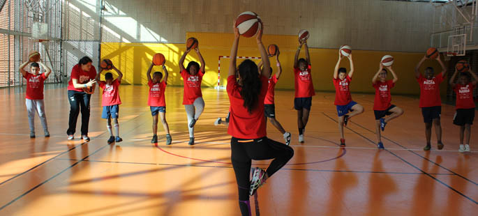 Pictured is Helena Knorr, Ph.D., teaching yoga to youth in the Euroleague Basketball's ONE TEAM program.