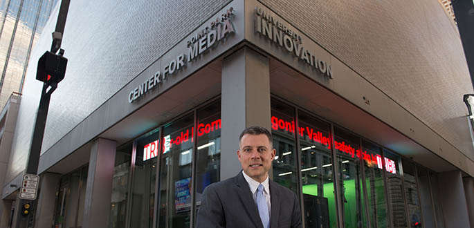 Andrew Conte sits outside of Point Park University's new Center for Media Innovation. Photo | Christopher Rolinson