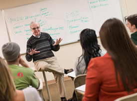 Pictured is Bob O'Gara, professor of public relations and advertising, teaching in the classroom.
