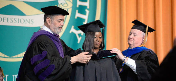 Pictured are Professors Gregory Rogers, J.D., and Richard Linzer, J.D., hooding a graduate student at Point Park's 2016 Hooding Ceremony. | Photo by Chris Rolinson