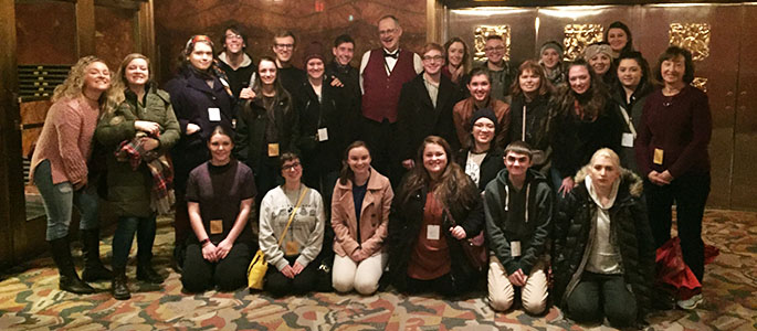 Students pose for a photo with their tour guide after a comprehensive tour of the iconic Radio City Music Hall.