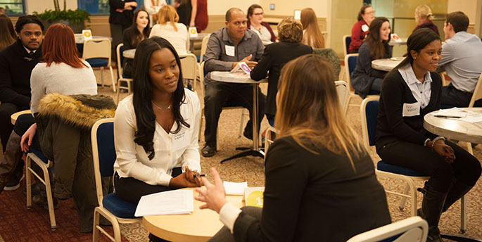 In a room in Lawrence Hall, Point Park students engage in conversations with alumni and other working professionals at an event called