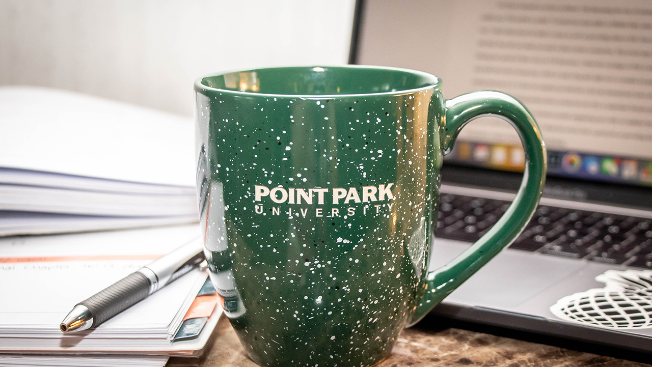 Pictured is a laptop and Point Park University mug. Photo by Mallory Neil