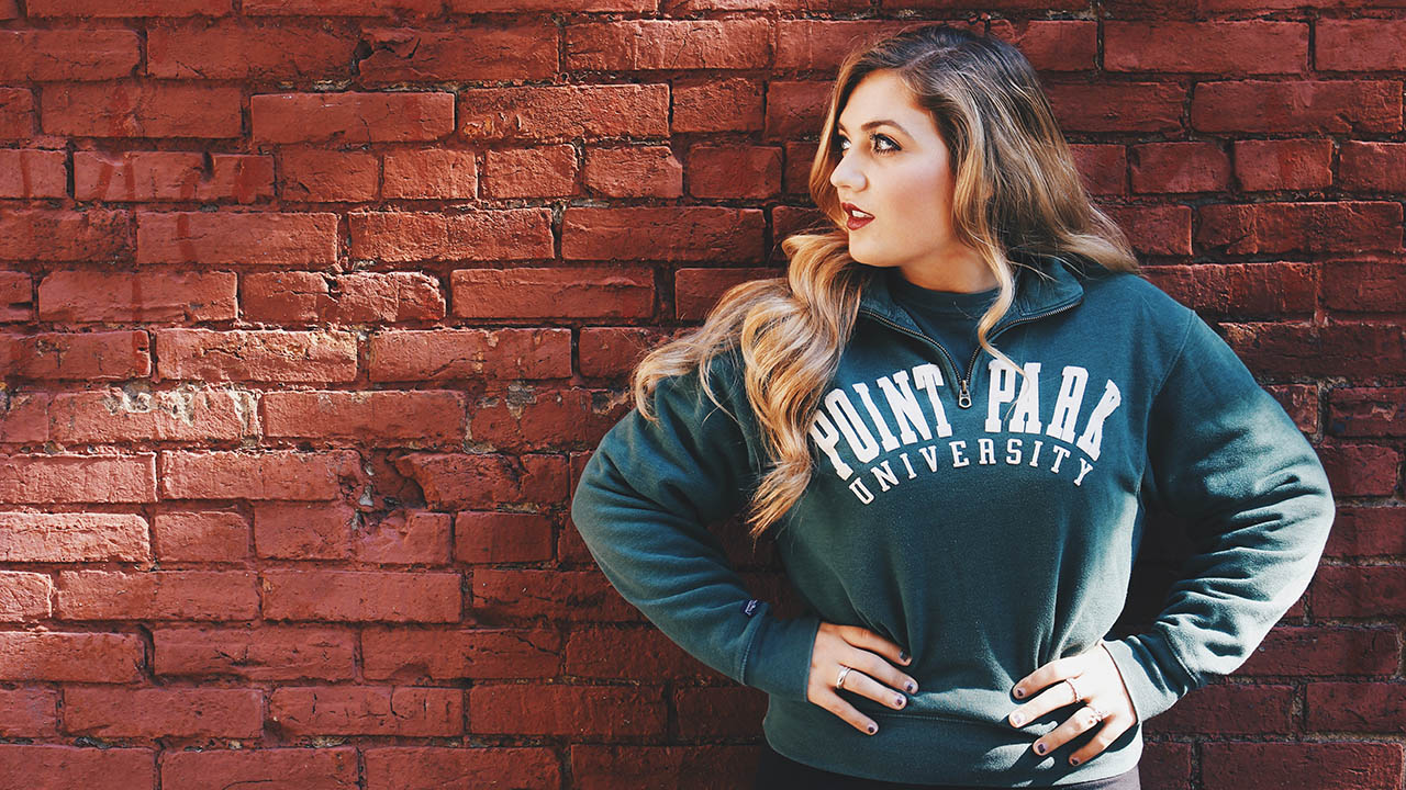Pictured is a female student wearing a Point Park University sweatshirt in front of an exposed brick background.