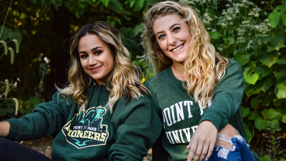 Two students wearing Point Park apparel in front of fall foilage